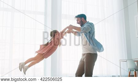 Young father circling little daughter in home interior