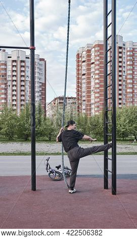 Older Asian Man Training On Sports Ground In City Park Against Background Of Cityscape. Lifestyle
