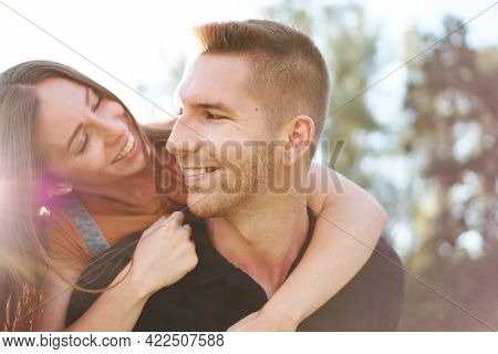 Young Caucasian Couple Smiling And Looking Into Each Other's Eyes - Boyfriend Carrying His Girlfrien