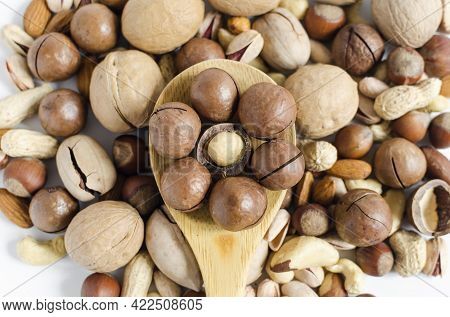 Macadamia Nuts In A Wooden Spoon On The Background Of A Scattering Of Different Nuts Assorted Nuts.