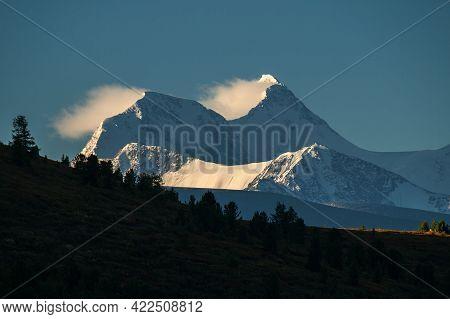 Mountain Peak In The Morning Sun. The Wind Blows Snow From The Mountain Peak. Mount Belukha, Altai.
