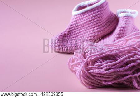 A Skein Of Pink Yarn With Knitted Shoes On A Pink Kopi Space Background. Home Knitting.