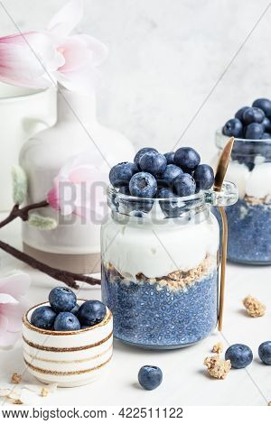 Blueberry Butterfly Pea Flower Parfait In Glass Jars On A White Background. Blue Matcha Chia Pudding