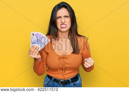 Beautiful hispanic woman holding 20 swedish krona banknotes annoyed and frustrated shouting with anger, yelling crazy with anger and hand raised
