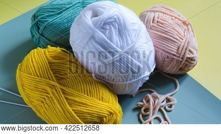 Skeins Of Multicolored Yarn On A Two-tone Yellow-green Background Close-up From Above. Yarn For Knit