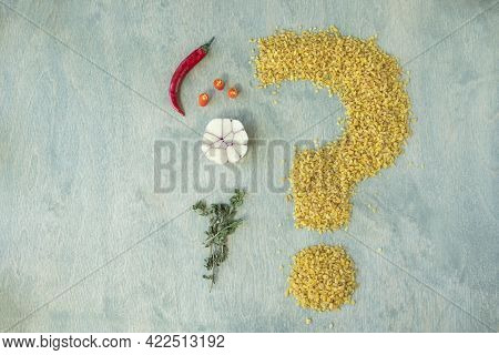 Bulgur With Spices On A Green Wooden Background. Beans Of Bulgur Shaped Like A Question Mark With Ch