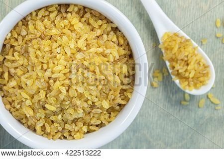 Close Up Yellow Bulgur On A Green Wooden Background. Beans Bulgur In White Plate With Spoon. Flat La