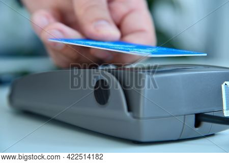 Hand Holding Credit Card Hear Nfc Pos Terminal. Transaction Pay And Shopping Concept. Close Up