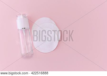 Reusable Glass White Bottle For Oil, Cream, Lotion Or Serum And Reusable Cotton Pads On A Pink Backg