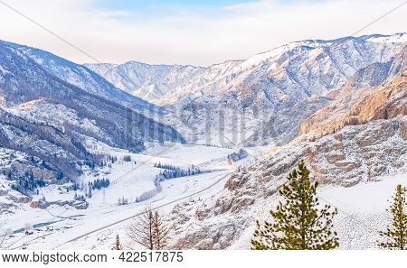 Winter Snowy Landscape Of The Valley Among The High Rocky Mountains With A Highway, Road And A Villa