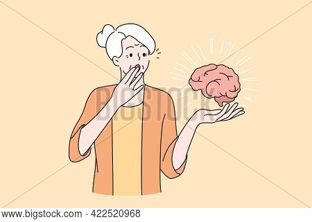 Mental Health Of Elderly People Concept. Senior Surprised Woman With Grey Hair Holding Brain Coverin