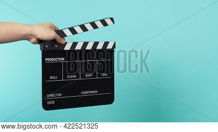 Hand Is Holding Black Clapper Board Or Movie Clapperboard Or Slate On Green Mint Or Tiffany Blue Bac