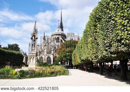 Notre Dame De Paris. The Building Of The Cathedral From The Side Of The Park. View Of The Cathedral.