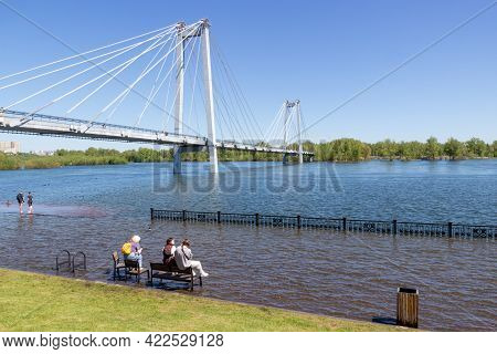 Krasnoyarsk, Russia - June 1, 2021: People Are Resting On A Benchs Against The Background Of A Cable
