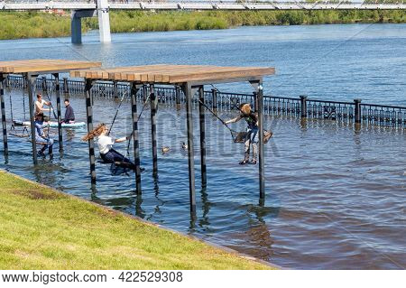 Krasnoyarsk, Russia - June 1, 2021: Children Are Swinging On A Swing Against The Background Of The F