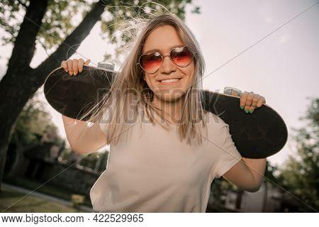 Smiling blonde girl holding her skateboarde