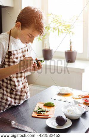Young Boy Peeling Avocado Preparing Sushi At Home