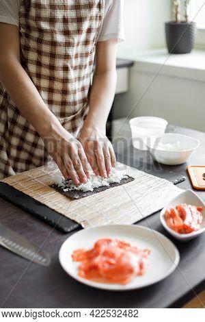Young Teenage Boy Making Maki Sushi At Home