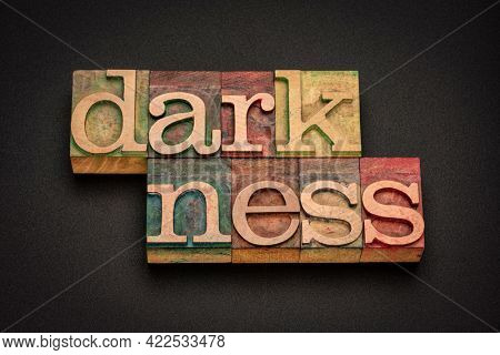 darkness word abstract in vintage letterpress wood type against black background, total absence of light