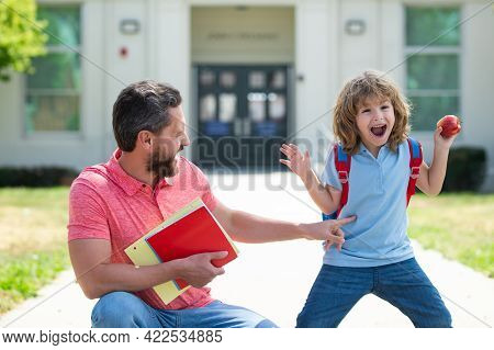 Father Walking Son To School. Parent And Pupil Of Primary School Schoolboy With Backpack At School Y