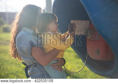 Young Mother And Baby Call On A Landline Street Phone In Telephone Booth In The Village In Summer. W
