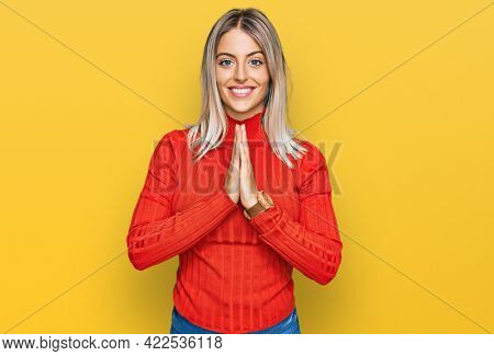 Beautiful blonde woman wearing casual clothes praying with hands together asking for forgiveness smiling confident.