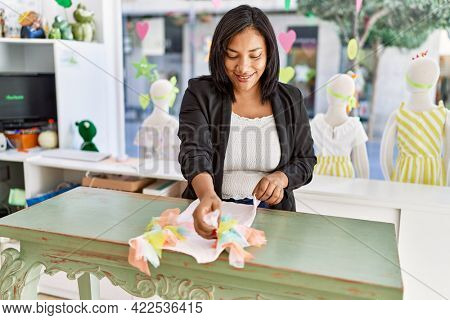 Hispanic woman working as shop assistant at children clothes small retail trade. sales assistant smiling happy at shopping counter while folding shirt.