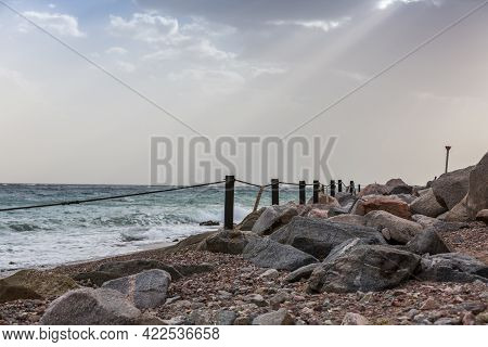 Fencing By The Sea. Storm To The Red Sea. Dramatic Landscape With Sunbeams. Rope And Sign No Swimmin