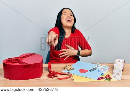 Beautiful hispanic woman with nose piercing doing handcraft creative decoration laughing at you, pointing finger to the camera with hand over body, shame expression