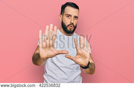 Young man with beard wearing casual white t shirt moving away hands palms showing refusal and denial with afraid and disgusting expression. stop and forbidden.