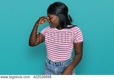 African young woman wearing casual striped t shirt smelling something stinky and disgusting, intolerable smell, holding breath with fingers on nose. bad smell