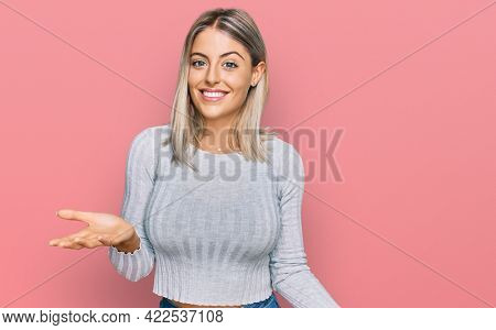 Beautiful blonde woman wearing casual clothes smiling cheerful with open arms as friendly welcome, positive and confident greetings