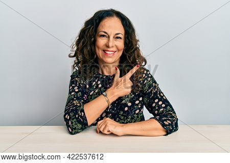 Beautiful middle age woman wearing casual clothes sitting on the table cheerful with a smile of face pointing with hand and finger up to the side with happy and natural expression on face