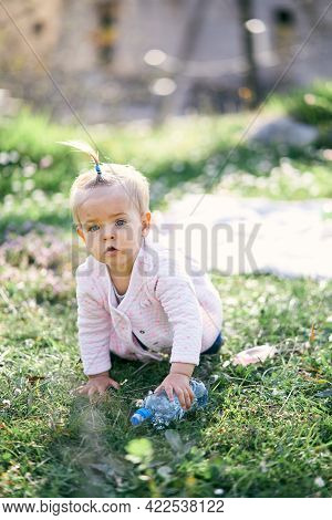 Pensive Little Girl With A Ponytail On Her Head Crawls Along A Green Lawn Among Flowers And Holds A