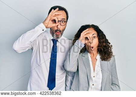 Middle age couple of hispanic woman and man wearing business office uniform doing ok gesture shocked with surprised face, eye looking through fingers. unbelieving expression.