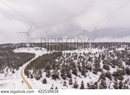 Aerial Shot Of Wind Turbine Farm At Snowy Highlands In Turkey At Cloudy Spring Day
