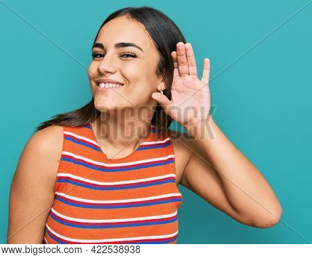 Young brunette woman wearing casual clothes smiling with hand over ear listening an hearing to rumor or gossip. deafness concept.