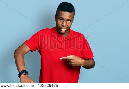 Young african american man wearing casual red t shirt in hurry pointing to watch time, impatience, upset and angry for deadline delay