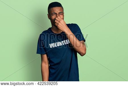 Young african american man wearing volunteer t shirt smelling something stinky and disgusting, intolerable smell, holding breath with fingers on nose. bad smell