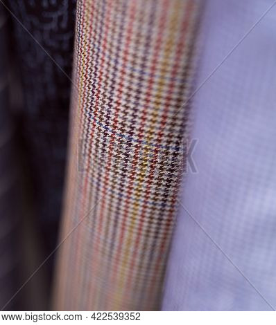 Closeup Bunch Of Warm Linen Tweed Textile Rolls In Different Colors And Patterns. Fabrics Retail Sto