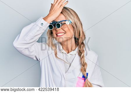 Beautiful young blonde woman wearing optometry glasses surprised with hand on head for mistake, remember error. forgot, bad memory concept.