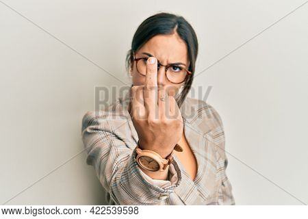 Young brunette woman wearing business jacket and glasses showing middle finger, impolite and rude fuck off expression