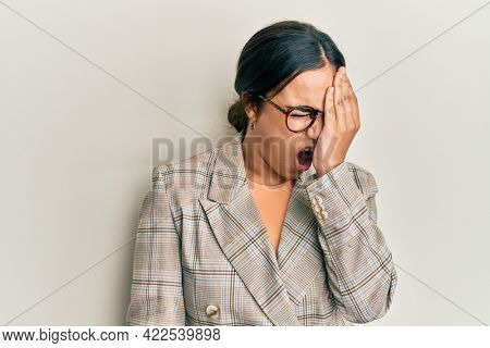 Young brunette woman wearing business jacket and glasses yawning tired covering half face, eye and mouth with hand. face hurts in pain.
