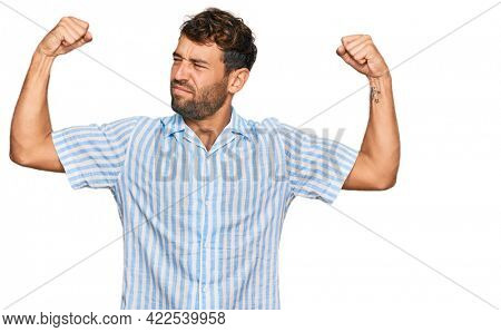 Handsome young man with beard wearing casual fresh shirt showing arms muscles smiling proud. fitness concept.