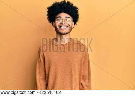 Young african american man with afro hair wearing casual winter sweater with a happy and cool smile on face. lucky person.