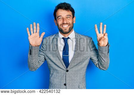Handsome man with beard wearing business suit and tie showing and pointing up with fingers number eight while smiling confident and happy.