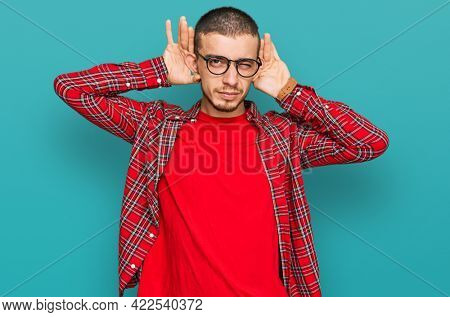 Hispanic young man wearing casual clothes trying to hear both hands on ear gesture, curious for gossip. hearing problem, deaf