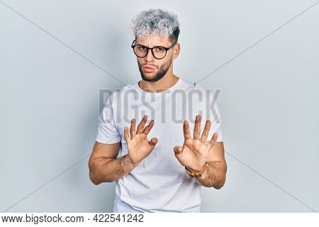 Young hispanic man with modern dyed hair wearing white t shirt and glasses moving away hands palms showing refusal and denial with afraid and disgusting expression. stop and forbidden.
