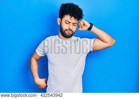 Young arab man with beard wearing casual white t shirt stretching back, tired and relaxed, sleepy and yawning for early morning