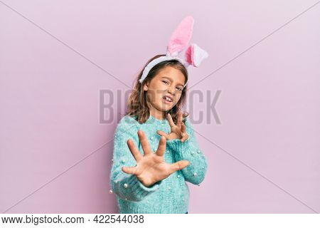 Little beautiful girl wearing cute easter bunny ears disgusted expression, displeased and fearful doing disgust face because aversion reaction. with hands raised